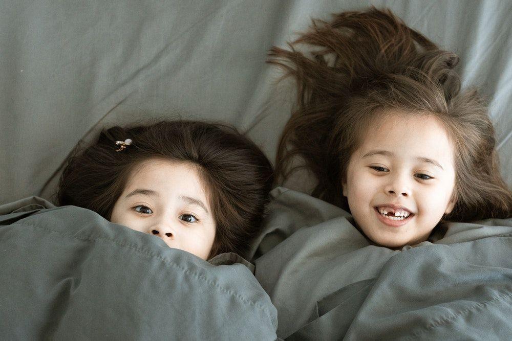 dua anak perempuan bersiap tidur dengan selimut
