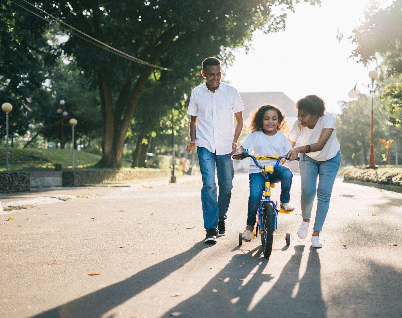 anak bermain sepeda ditemani orang tua