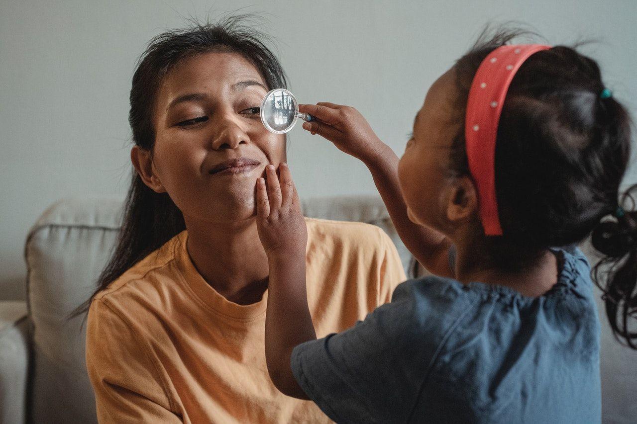 anak perempuan bermain peran dokter bersama ibu