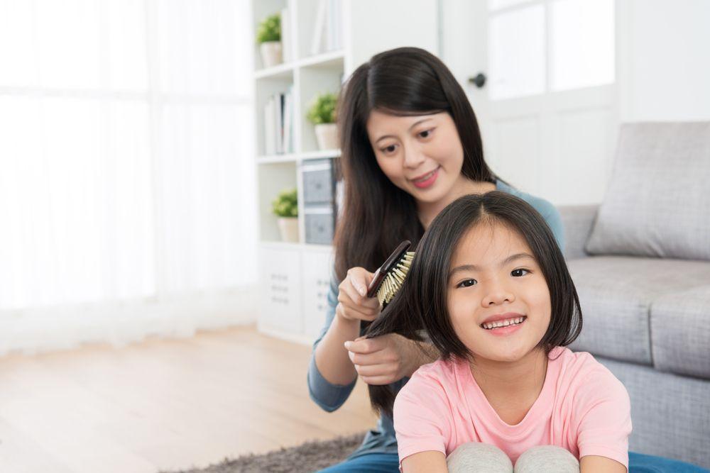 ibu menyisir rambut anak perempuannya