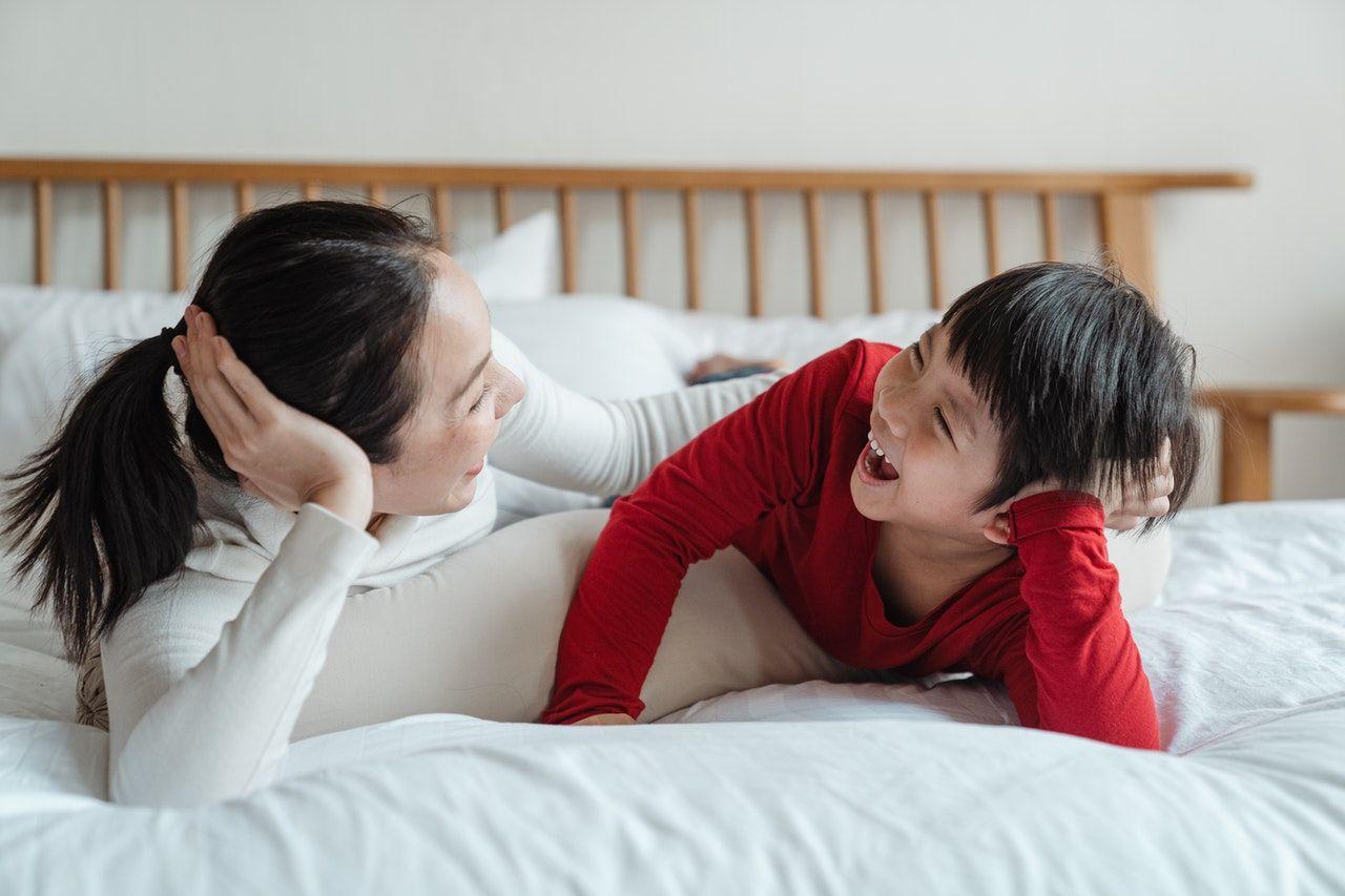 anak dan ibu tertawa bersama menunjukkan kelekatan